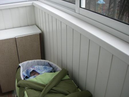 Ребенок спит на балконе.
